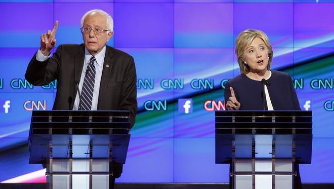 Hillary Clinton, right, and U.S. Sen. Bernie Sanders of Vermont speak at the Democratic presidential debate.