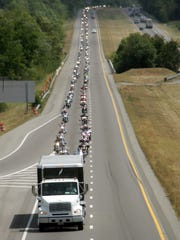 "Hundreds of motorcycles follow the truck that holds ""The Wall that Heals"" replica of The Wall in 2007 while traveling to Dickson."