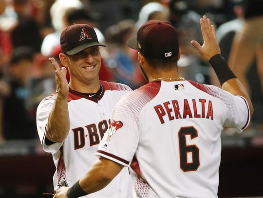 Diamondbacks manager Torey Lovullo (left) slaps hands