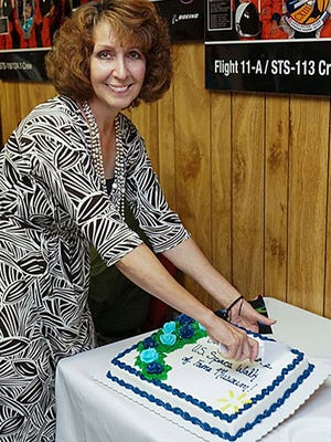 Tara Dixon Engel slices the cake as the U.S. Space Walk of Fame celebrates the purchase of its permanent facility last month. Dixon Engel has taken over as the nonprofit''r executive director.