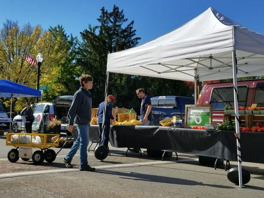 Dakoda Lubbert helps collects food donations from the Downtown FDL Farmers Market produce vendors.