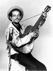 This 1944 file photo shows Woody Guthrie, singer, songwriter,