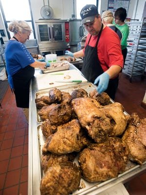Heidi Silivos, left, and Paul Brown prepare lamb Wednesday, Oct. 11, 2017, for this weekend's Pensacola Greek Festival.