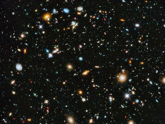 This handout composite image provided by NASA shows the visible and near infrared light spectrum collected from NASA's Hubble Space Telescope over a nine-year period. The Hubble Space Telescope has captured our cosmos at its most colorful. A new NASA panorama looking deep and far into the universe for the first time includes ultraviolet light, which is normally not visible to the human eye. It shows up in the photo as bright baby blue with spinning galaxies, which are about 5 to 10 billion years old, not too old or young in cosmic terms. The photo was taken over 841 orbits of the telescope and shows about 10,000 multi-colored galaxies. (AP Photo/NASA)