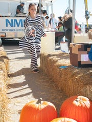 Merissa Cano tries out the pumpkin ring toss at the New Mexico Department of Agriculture booth Saturday during the third Ag Day Street Fair.