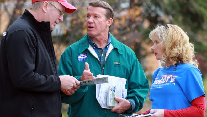 Steve Pendery, center, incumbent Campbell County judge-executive, talks with Keith Brown of Fort Thomas as he campaigns door-to-door for the upcoming election in which he is seeking another term as county leader. At right is Pendery's wife, Dana. Brown said he is an independent and hasn't made up his mind about whom he will vote for.