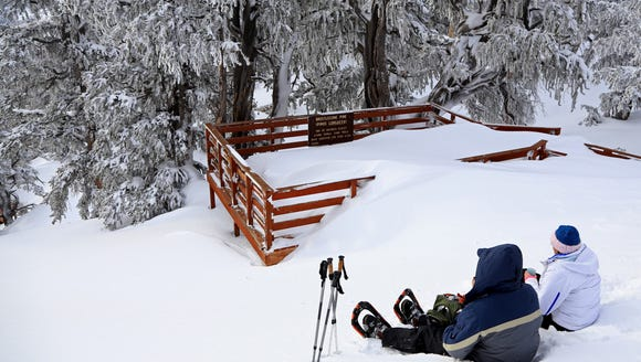 Snowshoers stop for a break at the overlook along the