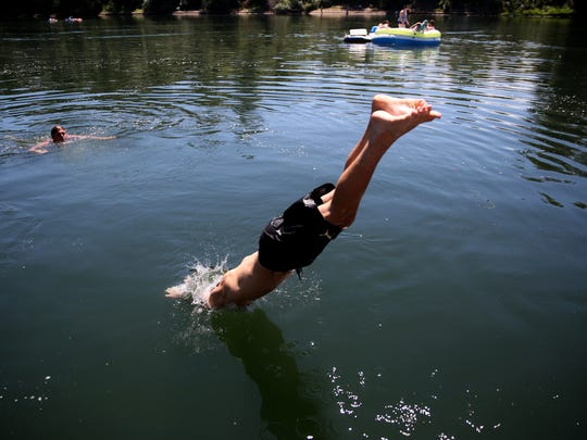 Phillip Magvas, 14, of Mesa, Ariz., dives into the Willamette River as Alan Sullivan, 17, of Keizer, and a raft float by at Keizer Rapids Park on Sunday, July 15, 2018. A heat advisory is in effect for Salem and Keizer through Monday evening.