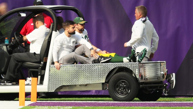 Aaron Rodgers of the Green Bay Packers rides a cart into the locker room after being injured during the first quarter.
