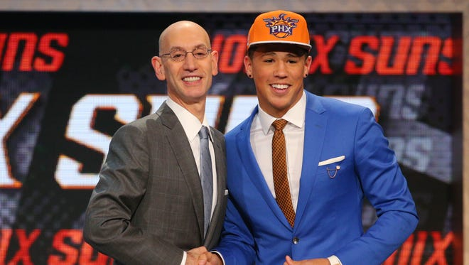 Devin Booker greets NBA commissioner Adam Silver after being selected as the number 13th overall pick by the Suns in 2015 NBA draft.