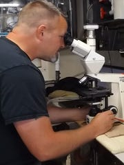 Scientist Anthony Odell examines samples of toxic algae through a microscope.