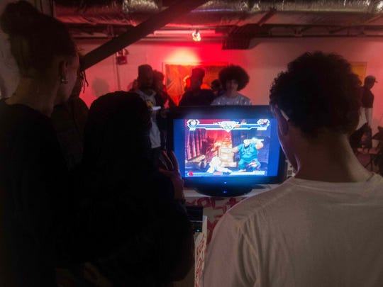 Teens play video games during a Plug Worldwide showcase at the Chris White Gallery in Wilmington last month.