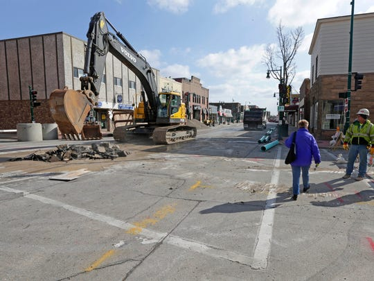A pedestrian crosses near the corner of S. 74th St. and Greenfield Avenue as work continues. West Allis discovered a collapsing sanitary sewer over the weekend that could have turned into a sinkhole. So they shut down Greenfield Avenue between 70th and 76th St. in West Allis to start the repair on Monday, March 12, 2018.