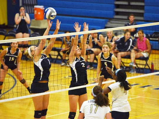 John Jay's Nicole Nardone, left, and Cassidy McDonald, right, attempt to block the ball in Thursday's game against Our Lady of Lourdes.