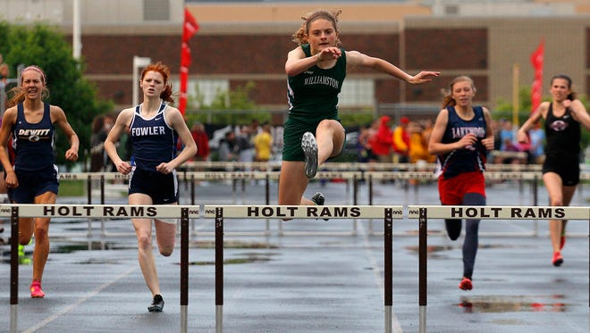 Williamston's Grace Lounsbury, center, goes over the last hurdle well ahead of the pack to win the 300 hurdles during the Honor Roll track meet Tuesday, May 26, 2015, at Holt High School in Holt, Mich.