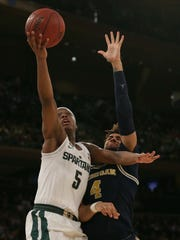 Michigan State Spartans guard Cassius Winston puts up a shot against Michigan Wolverines forward Isaiah Livers (4) during the first half of a semifinal game of the 2018 Big Ten Tournament at Madison Square Garden.