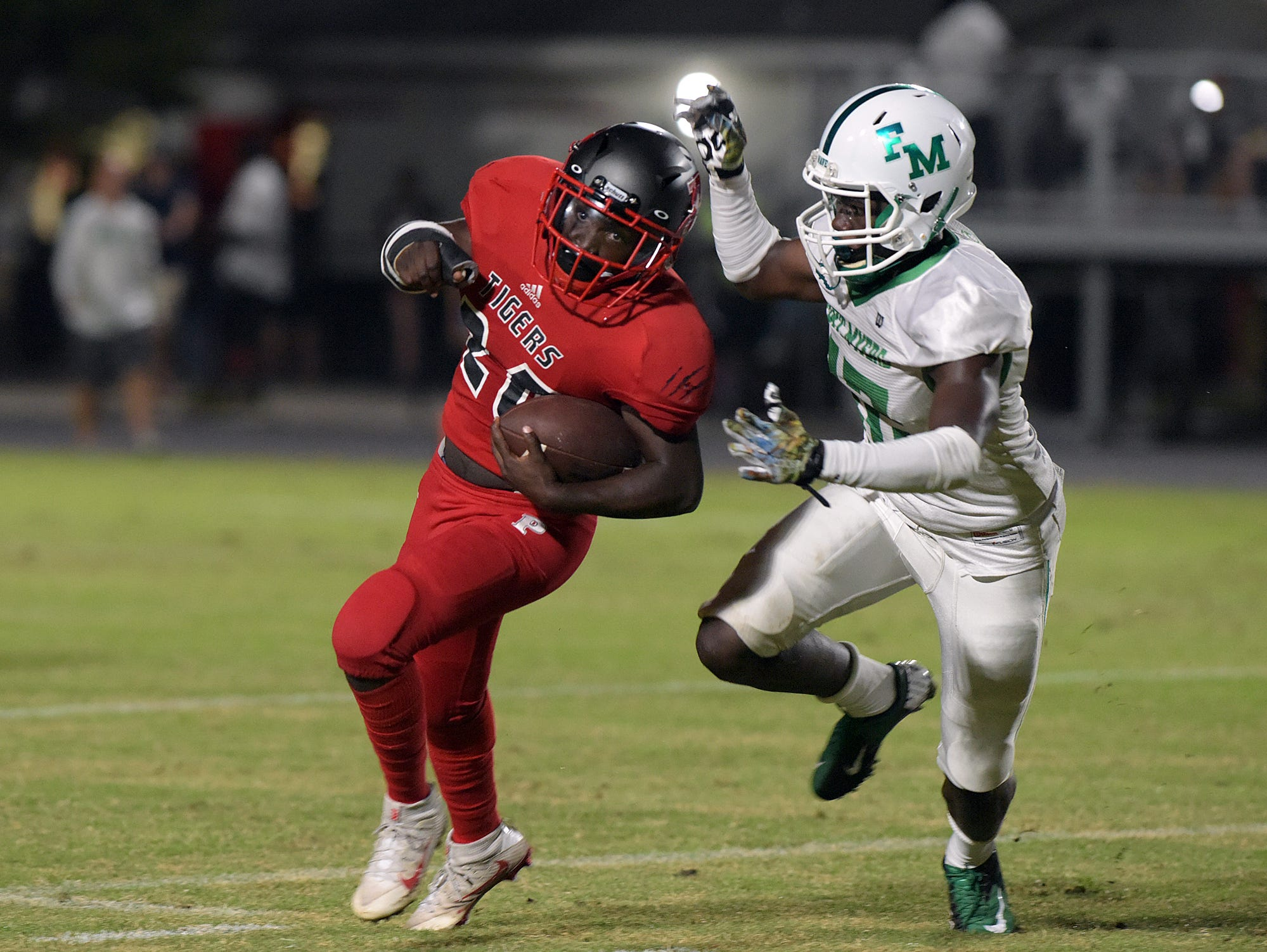 Palmetto's Herman White IV runs the ball as Fort Myers' J.D. Thomas closes in for the tackle during Friday night's rain-delayed game against Fort Myers at Palmetto.