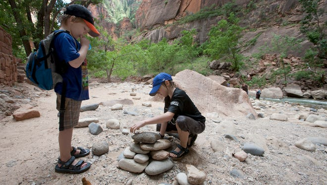 Max Burkett, left, sips water from the tube of his CamelBak Mini M.U.L.E. hydration pack while watching his brother, Ethan Burkett, build a cairn of stones along the banks of the Virgin River at the mouth of the Narrows in Zion National Park on July 19, 2011.