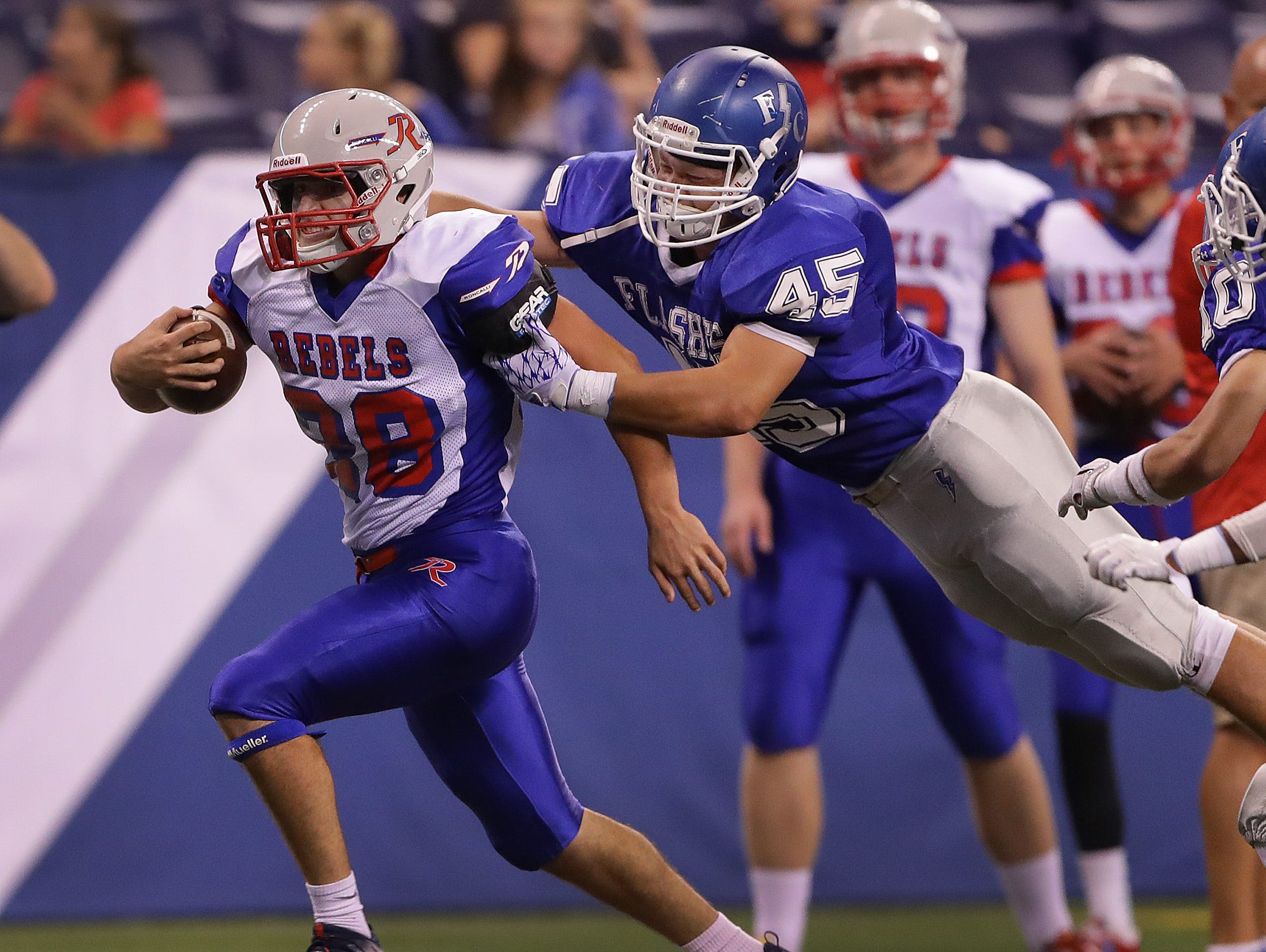 Roncallli's Kenny Gillum (28) is hit by Franklin Central's Chris Ford (45) in the first half of their game. The Franklin Central Flashes played the Roncallli Rebels in high school football Friday, August 26, 2015, evening at Lucas Oil Stadium.