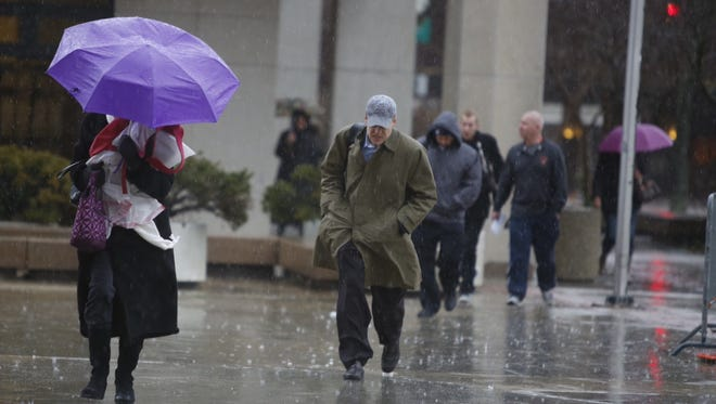 People tread through a downpour near the county courthouse in White Plains as a gusty Nor'easter bears down on the Lower Hudson Valley Tuesday, Dec. 9.