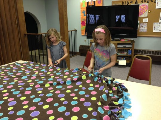 Libby Thompson and Ana Sewall participate as volunteers for St. John's Episcopal outreach by tying blankets that were donated to Aspirus Hospice House.