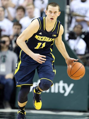 Michigan Wolverines guard Nik Stauskas (11) brings the ball up court against the Michigan State Spartans during the 1st half of a game at Jack Breslin Student Events Center.