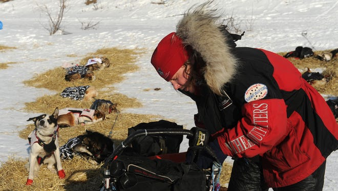 FILE - Iditarod musher Aliy Zirkle, from Two Rivers, Alaska, works on her gear at the White Mountain checkpoint during the 2014 Iditarod Trail Sled Dog Race in this March 10, 2014 file photo. Zirkle, who has finished second the past three years, said she's learned there's a limit to how far you can strip down a sled to make it lighter. (AP Photo/The Anchorage Daily News, Bob Hallinen, File)