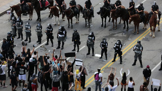 Protesters stand in the middle of Broad Street in Downtown on May 30, 2020, as Columbus Division of Police officers and mounted patrol attempt to move them from the area.