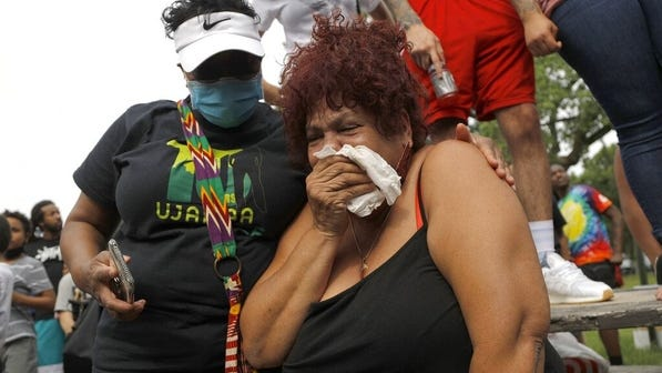Women react during protests in Minneapolis, where a shooting overnight left one man dead and injured 11 others.