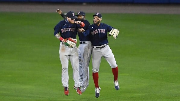 Red Sox left fielder Alex Verdugo, left, center fielder Jackie Bradley Jr. and right fielder Kevin Pillar celebrate their win over the Toronto Blue Jays on Tuesday in Buffalo, N.Y.