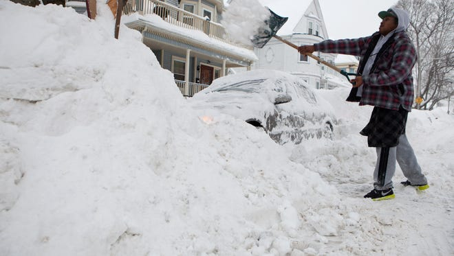 A resident digs his car out from the snow on Feb. 9, 2015, in the Dorchester neighborhood of Boston.