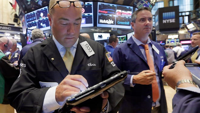 Trader Christopher Morie, left, works on the floor of the New York Stock Exchange, Thursday, Aug. 13, 2015.