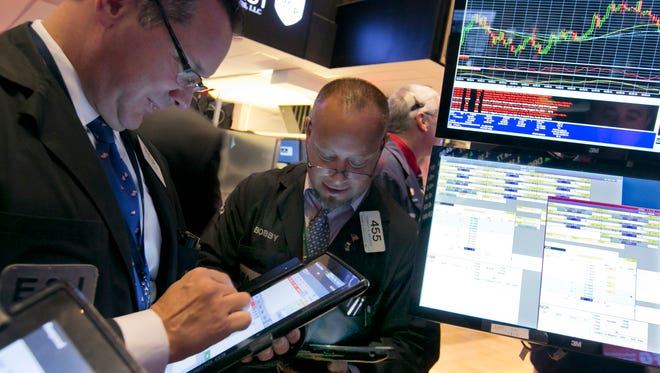 Traders Edward Curran, left, and Robert Arciero work on the floor of the New York Stock Exchange, Friday, Oct. 2, 2015.  (AP Photo/Richard Drew)