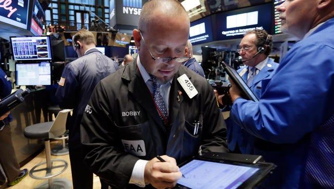 Trader Robert Arciero, center, works on the floor of the New York Stock Exchange, Monday, Oct. 12, 2015.  (AP Photo/Richard Drew)