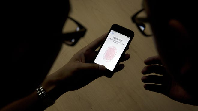 XcodeGhost is a malware that has infected at least 3500 known iOS apps, all of which made it into the App Store. In this file photo, users try the fingerprint lock system on an iPhone.
