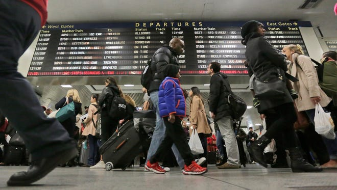 In this Nov. 25, 2015 file photo, Amtrak passengers walk to their gates in New York's Pennsylvania Station.