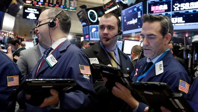 FILE - In this Dec. 16, 2015 photo, traders Gordon Charlop, left, Nathan Wisniewski, center, and Gregory Rowe, work on the floor of the New York Stock Exchange.  (AP Photo/Richard Drew)