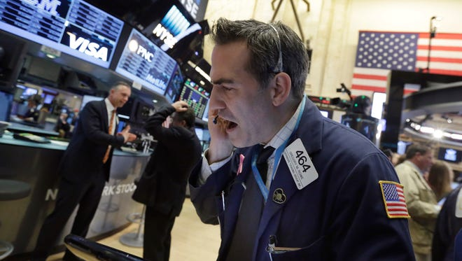 Trader Gregory Rowe, center, works on the floor of the New York Stock Exchange, Monday, March 28, 2016. (AP Photo/Richard Drew)