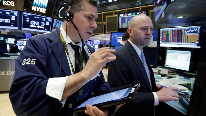 Trader William McInerney, left, and specialist Jay Woods work on the floor of the New York Stock Exchange, Wednesday, March 30, 2016.   (AP Photo/Richard Drew)