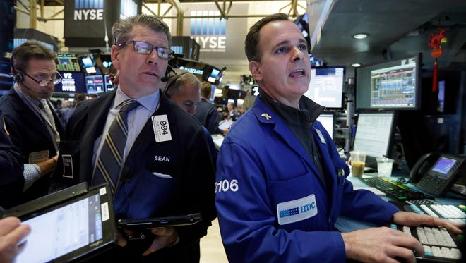 Trader Sean Spain, wearing a tie, and specialist John Alatzas, right, work on the floor of the New York Stock Exchange, Wednesday, March 30, 2016.  (AP Photo/Richard Drew)