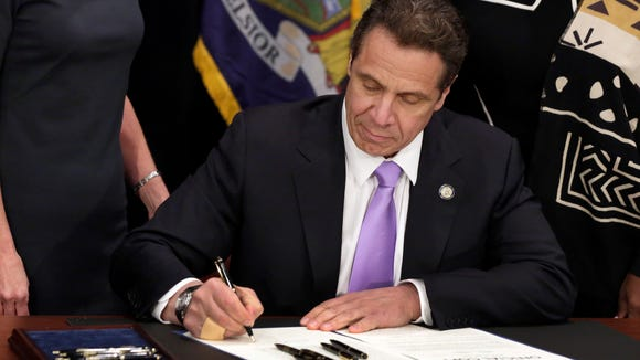 Gov. Andrew Cuomo signs a law that raises the minimum wage in New York on April 4, 2016.