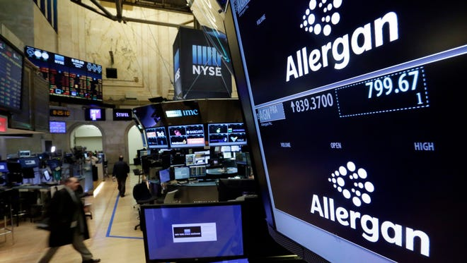Allegan logos appears on screens above its trading post on the floor of the New York Stock Exchange, Wednesday, April 6, 2016. The biggest U.S.-based drugmaker, Pfizer Inc., will stay put thanks to aggressive new Treasury Department rules that succeeded in blocking Pfizer from acquiring rival Allergan and moving to Ireland, on paper, to reduce its tax bill.  (AP Photo/Richard Drew)