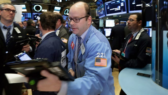 Trader Peter Mancuso, center, works on the floor of the New York Stock Exchange, Monday, April 11, 2016.  (AP Photo/Richard Drew)