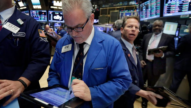 Trader Brian Sears, center, works on the floor of the New York Stock Exchange, Monday, May 9, 2016.  (AP Photo/Richard Drew)