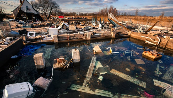 A still running water pipe floods the foundation of a home destroyed by the storm surge of superstorm Sandy in the Staten Island borough neighborhood of Oakwood in New York, November 28, 2012.  REUTERS/Lucas Jackson (UNITED STATES - Tags: DISASTER ENVIRONMENT) - RTR3AZWB
