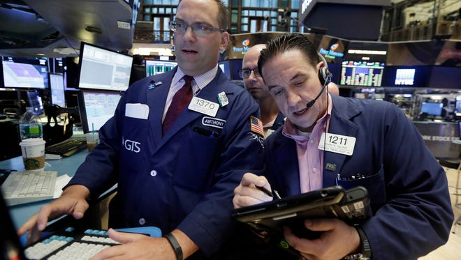 Specialists Anthony Matesic, left, and Mario Picone, center, work with trader Tommy Kalkas on the floor of the New York Stock Exchange, Friday, June 3, 2016.  (AP Photo/Richard Drew)