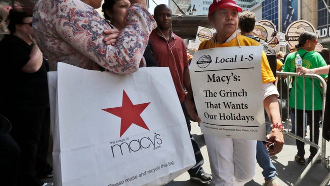 FILE - In this Thursday, June 2, 2016, file photo, a shopper and a demonstrator pass on the sidewalk during a rally by union workers outside Macy's flagship store in New York. Workers at the iconic store are threatening to strike if contract negotiations fail. The current contract is set to expire at midnight Wednesday, June 15. Macy's sees the threat of the strike as real and has placed ads seeking temporary workers. (AP Photo/Richard Drew, File)