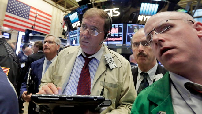 Jonathan Niles, center, works with fellow traders on the floor of the New York Stock Exchange, Wednesday, June 29, 2016. (AP Photo/Richard Drew)