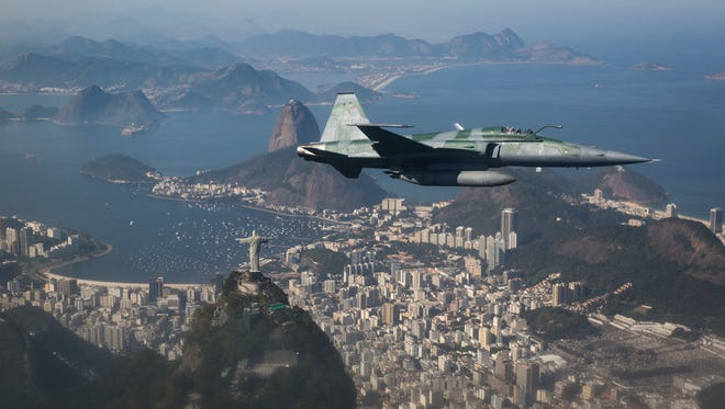 A F-5 fighter flies over the Christ the Redeemer statue, Guanabara Bay and the Sugar Loaf mountain, photographed through a window, while intercepting another aircraft during a Brazilian Air Force presentation for the press ahead of the Olympic games in Rio de Janeiro, Brazil July 14.