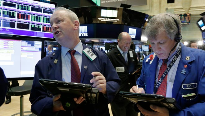 Trader James Riley, left, and Richard Newman, right, work on the floor of the New York Stock Exchange, Thursday, July 14, 2016. (AP Photo/Richard Drew)